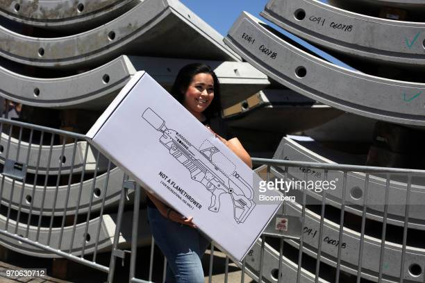An attendee holds a box containing a Boring Co. Flamethrower during the company's Not-a-Flamethrower Party outside of the Space Exploration...