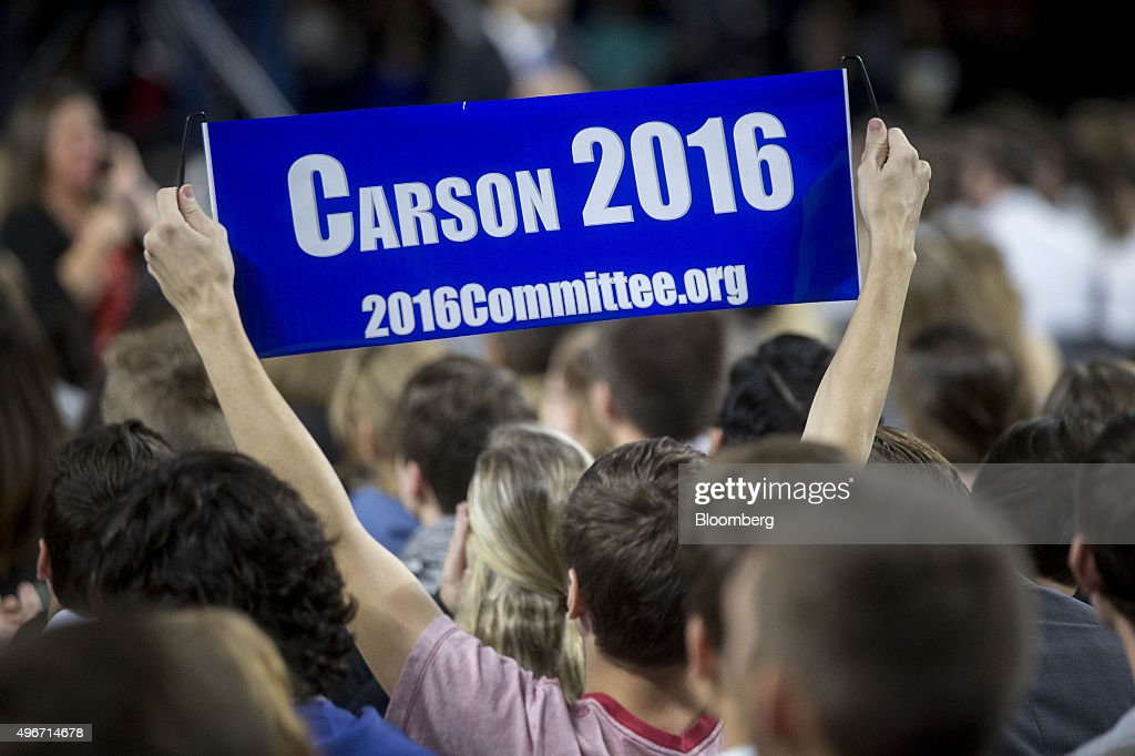 An attendee holds a 'Carson 2016' sign before Ben Carson, 2016 Republican presidential candidate, not pictured, speaks during a Liberty University Convocation in Lynchburg, Virginia, U.S., on Wednesday, Nov. 11, 2015. As retired neurosurgeon Carson has risen in the polls, media reports have revisited his accounts of acts of violence as a child, a key part of the redemption story he discusses on the campaign trail. Photographer: Andrew Harrer/Bloomberg via Getty Images