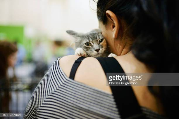 An attendee holds a cat at the adoption center at CatCon Worldwide 2018 at Pasadena Convention Center on August 4 2018 in Pasadena California