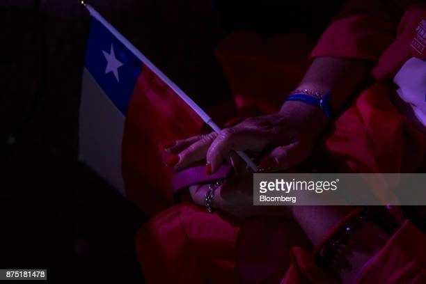 An attendee holds a Chilean national flag during a campaign rally for presidential candidate Sebastian Pinera in Santiago Chile on Thursday Nov 16...