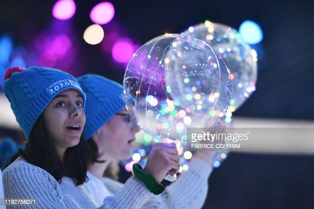 An attendee holds a clear balloon during the opening ceremony of the Lausanne 2020 Winter Youth Olympic Games in Lausanne on January 9 2020