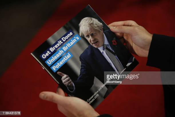 An attendee holds a copy of the manifesto in this arranged photograph at the Conservative Party's manifesto launch in Telford, U.K. On Sunday, Nov....