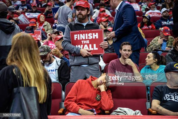 An attendee holds a Finish the Wall sign inside the Toyota Center ahead of a rally with US President Donald Trump and Senator Ted Cruz a Republican...