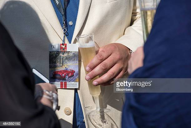 An attendee holds a glass of champagne during the 2015 Pebble Beach Concours d'Elegance in Pebble Beach California US on Sunday Aug 16 2015 Of the...