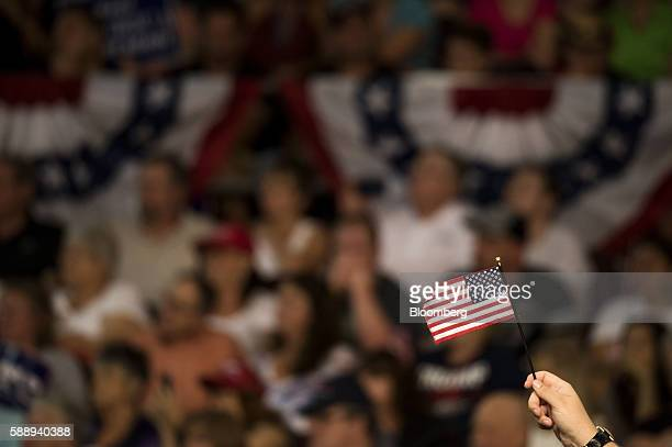 An attendee holds a miniature American flag during a campaign rally for Donald Trump 2016 Republican presidential nominee not pictured at the Erie...