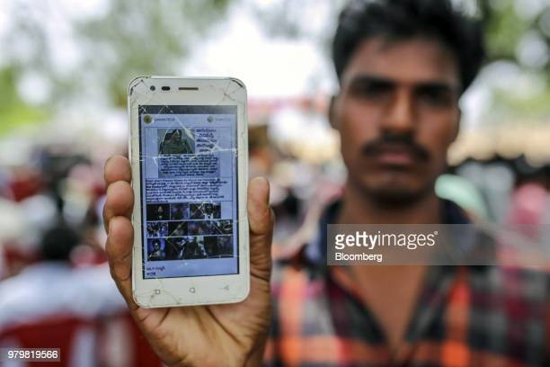 An attendee holds a mobile phone displaying a fake message shared on Facebook Incs WhatsApp messaging service while attending an event to raise...