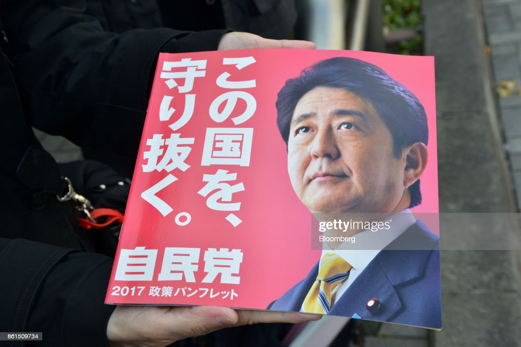 An attendee holds a pamphlet featuring a portrait of Shinzo Abe, Japans prime minister and president of the Liberal Democratic Party (LDP), during an election campaign rally in Sapporo, Hokkaido, on Sunday, Oct. 15, 2017. Abe looked set to retain his coalitions dominant position in parliament after the Oct. 22 general election, according to a series of large opinion surveys carried out by domestic media. Photographer: Eiji Ohashi/Bloomberg via Getty Images