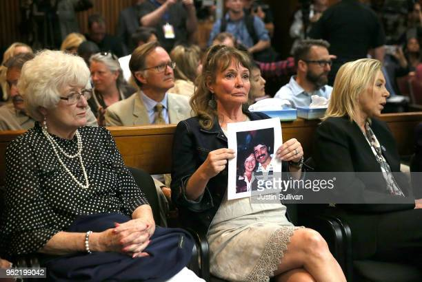 An attendee holds a photo of Cheri Domingo and her boyfriend Gregory Sanchez who were killed in 1981 as she sits in the courtroom during the...