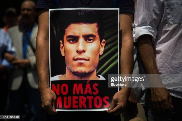 An attendee holds a poster displaying an image of Juan Pablo Pernalete allegedly killed during a protest against Venezuelan president Nicolas Maduro...