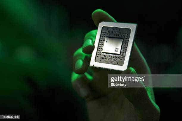 An attendee holds a processor for the Xbox One X console during the Microsoft Corp Xbox One X reveal event ahead of the E3 Electronic Entertainment...