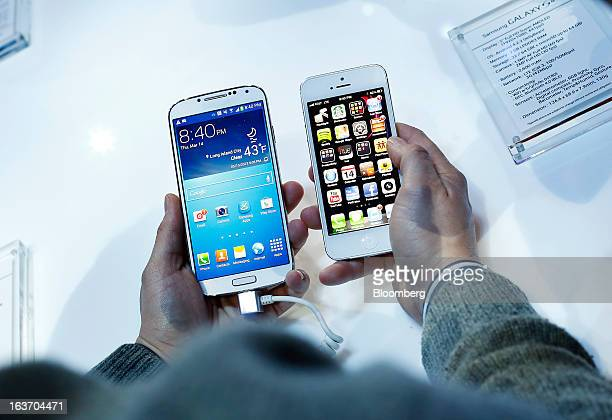 An attendee holds a Samsung Electronics Co Galaxy S4 smartphone left next to an Apple Inc iPhone 5 during an event at Radio City Music Hall in New...