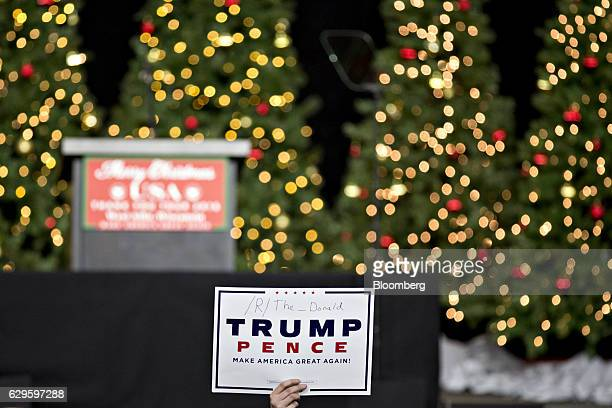 An attendee holds a sign as he waits for U.S. President-elect Donald Trump, not pictured, to arrive at an event in West Allis, Wisconsin, U.S., on...