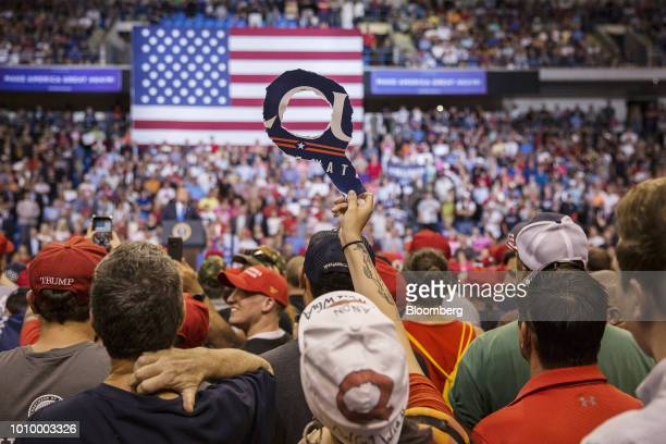 An attendee holds a sign of the letter Q as US President Donald Trump addresses the crowd during a rally in WilkesBarre Pennsylvania US on Thursday...