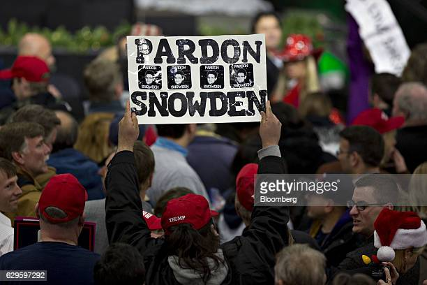 """An attendee holds a sign reading """"Pardon Snowden"""" as U.S. President-elect Donald Trump, not pictured, speaks during an event in West Allis,..."""