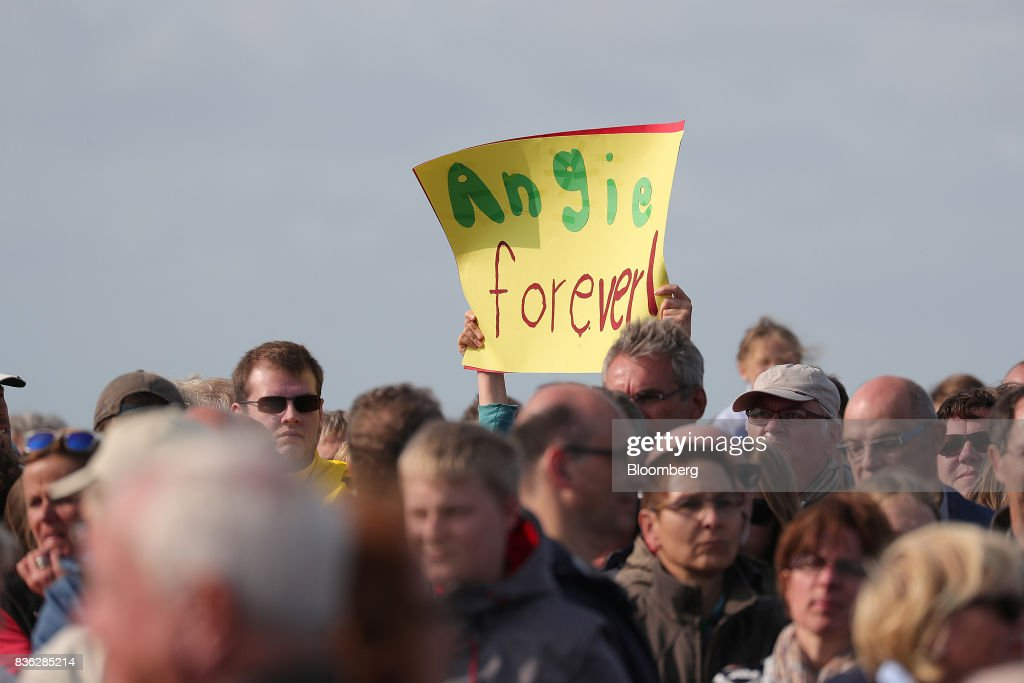 An attendee holds a sign that reads 'Angie forever' during an election campaign stop in Saint Peter-Ording, Germany, on Monday, Aug. 21, 2017. Merkel headed out on the campaign trail last week and quickly faced disruption by anti-immigration demonstrators, a reminder that the refugee crisis that sent her popularity plunging in 2016 remains a residual risk. Photographer: Krisztian Bocsi/Bloomberg via Getty Images