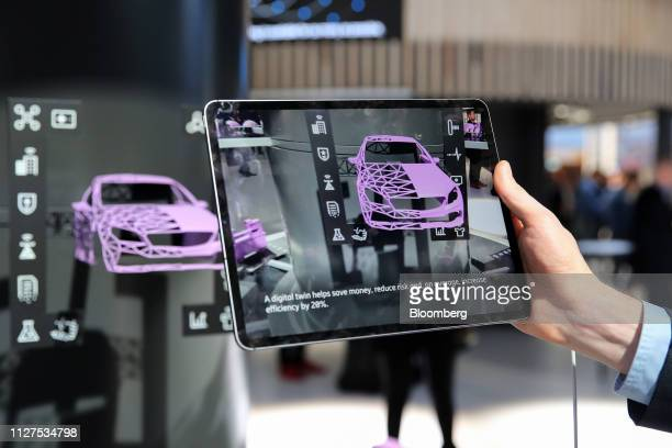 An attendee holds a tablet device displaying an automobile wireframe model during an augmented reality demonstration on the Ericsson AB stand on day...