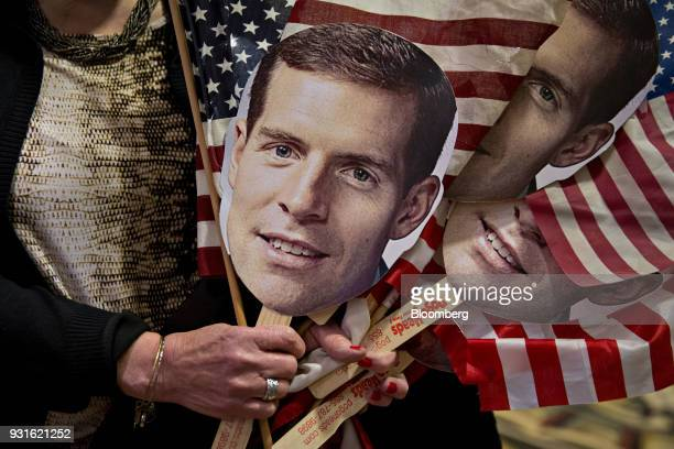 An attendee holds American flags and the portrait of Conor Lamb Democratic candidate for the US House of Representatives during an election night...