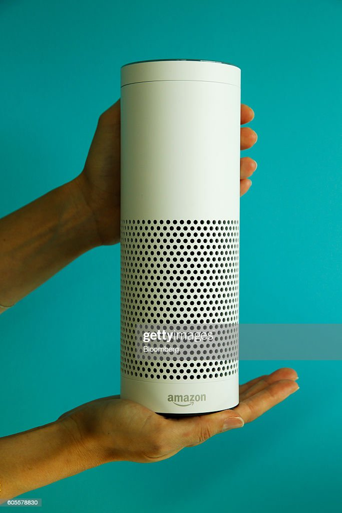 An attendee holds an 'Echo' device during the U.K. launch event for the Amazon.com Inc. Echo voice-controlled home assistant speaker in this arranged photograph in London, U.K., on Wednesday, Sept. 14, 2016. The Seattle-based company today announced that its Echo product line will be available in the U.K. and Germany starting in the fall, the first time the gadget will be available outside the U.S. Photographer: Luke MacGregor/Bloomberg via Getty Images