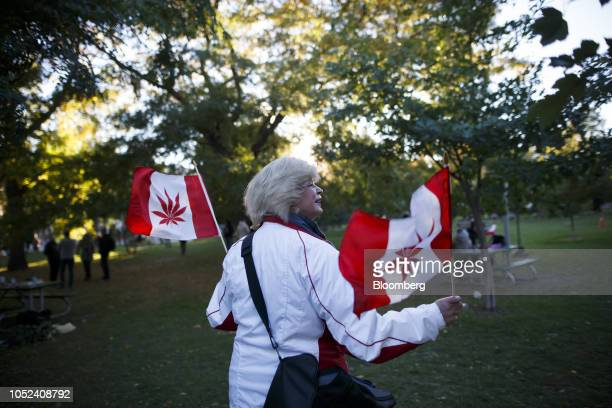 An attendee holds Canadian flags with cannabis leaves on it during a celebration of the legalization of cannabis at Trinity Bellwoods Park in Toronto...
