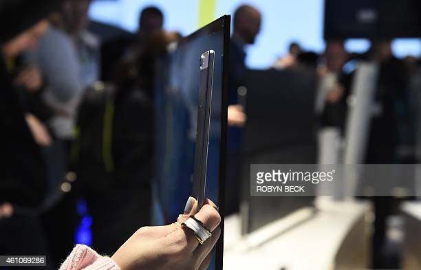 An attendee holds her personal smart phone besides a new Sony Bravia X900C 4K TV which is only 02 inches thick thinner than a Sony Xperia Z3...