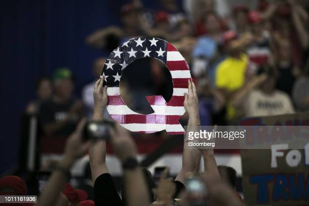 An attendee holds signs a sign of the letter Q before the start of a rally with US President Donald Trump in Lewis Center Ohio US on Saturday Aug 4...