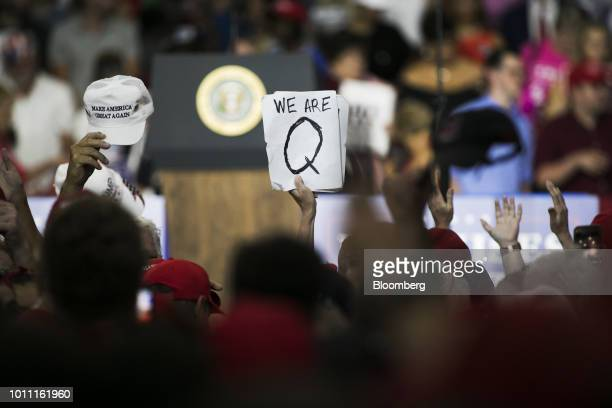 An attendee holds signs with the words We Are Q before the start of a rally with US President Donald Trump in Lewis Center Ohio US on Saturday Aug 4...