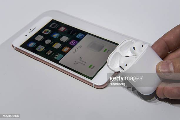 An attendee holds the Apple Inc AirPod wireless headphones next to the iPhone 7 Plus during an event in San Francisco California US on Wednesday Sept...