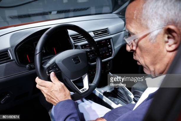 An attendee holds the steering wheel while inspecting the 2017 Espanola de Automovil Turismo Arona compact sports utility vehicle during a launch...
