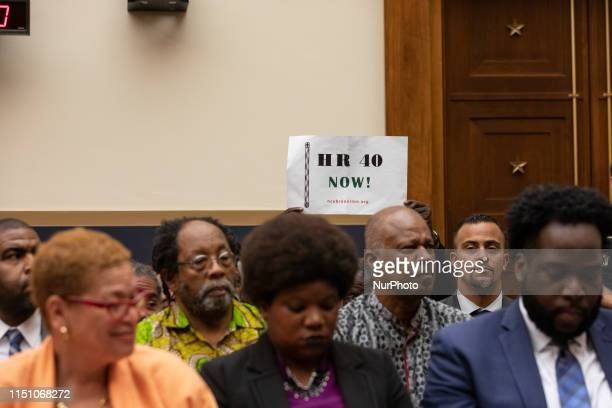 An attendee holds up a sign in support of HR 40, during the hearing on reparations for the descendants of slaves , before the House Judiciary...