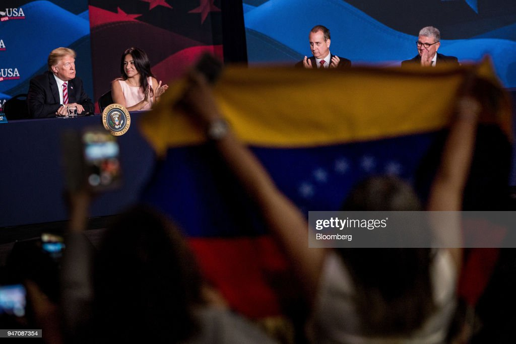 An attendee holds up a Venezuelan flag while U.S. President Donald Trump, left, speaks during roundtable discussion on tax cuts for Florida small businesses in Hialeah, Florida, U.S., on Monday, April 16, 2018. Trump accused China and Russia of devaluing their currencies, breaking from his own Treasury chief's view that no major trading partners are currency manipulators. Photographer: Scott McIntyre/Bloomberg via Getty Images