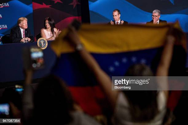 An attendee holds up a Venezuelan flag while US President Donald Trump left speaks during roundtable discussion on tax cuts for Florida small...