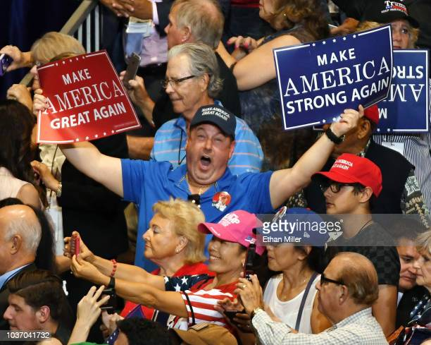 An attendee holds up signs as he sings along with the house music while waiting for US President Donald Trump to speak at a campaign rally at the Las...