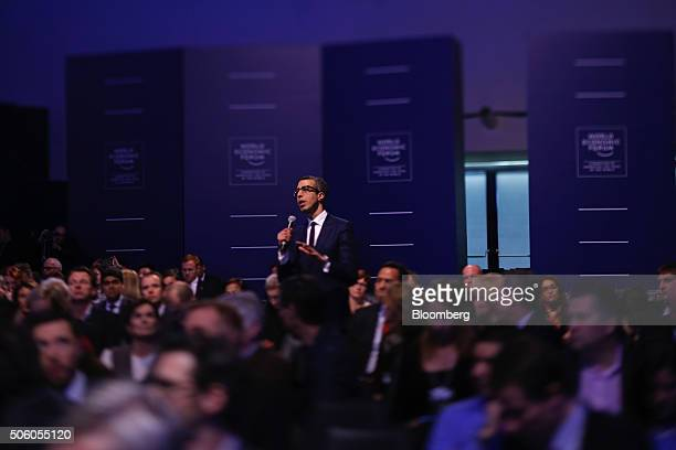 An attendee in the audience stands to ask a question during a special session at the World Economic Forum in this photograph taken with a tiltshift...
