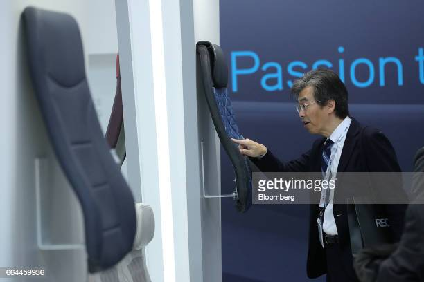 An attendee inspects a 'Delta' airline seat cover displayed at the Sabeti Wain pavilion at the 2017 Aircraft Interiors Expo in Hamburg, Germany, on...