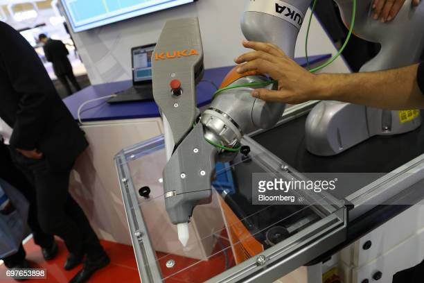 An attendee inspects a robotic arm manufactured by Kuka AG as it sits on display during the 53rd International Paris Air Show at Le Bourget in Paris...