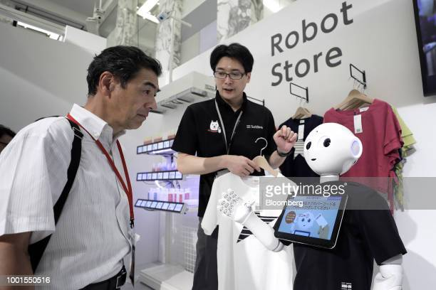 An attendee interacts with a SoftBank Group Corp Pepper humanoid robot at the SoftBank World 2018 event in Tokyo Japan on Thursday July 19 2018...