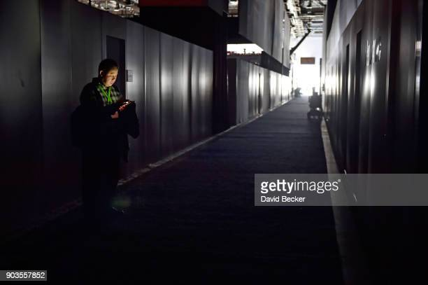 An attendee is illumiated by his smartphone during CES 2018 after the power was lost inside the central hall at the Las Vegas Convention Center on...