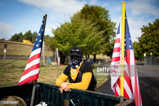 An attendee leans on the back of a pick-up truck ahead of a Proud Boys rally at Delta Park in Portland, Oregon on September 26, 2020. - Far-right...