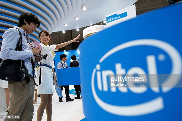 An attendee left speaks to a booth assistant in the Intel Corp booth at the CEATEC Japan 2013 exhibition in Chiba Japan on Tuesday Oct 1 2013 Intel...