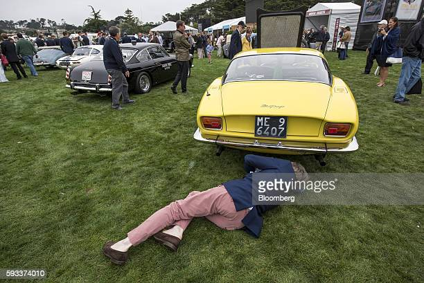 An attendee lies on the grass to photograph the underbody of a 1967 Iso Grifo GL Bertone Berlinetta motor vehicle during the 2016 Pebble Beach...