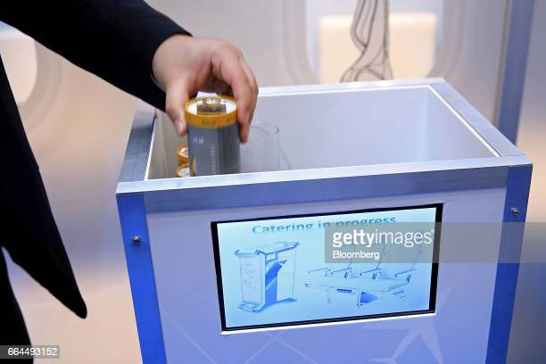 An attendee lifts a drinks can from a robotic waiter catering device manufactured by Altran Technologies SA at the Aircraft Interiors Expo in...