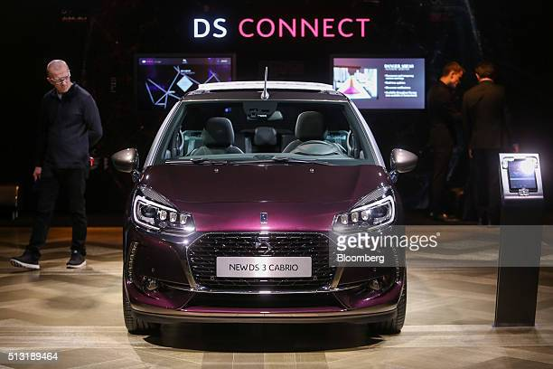 An attendee looks at a DS 3 Cabrio automobile produced by PSA Peugeot Citroen on the first day of the 86th Geneva International Motor Show in Geneva...
