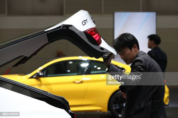 An attendee looks at a BMW AG 320d Gran Turismo vehicle during the press day of the Seoul Motor Show in Goyang South Korea on Thursday March 30 2017...