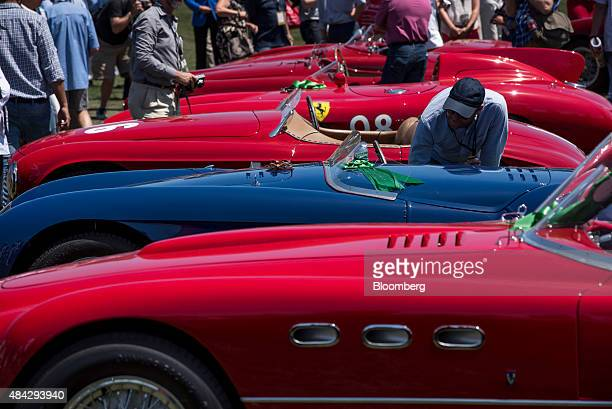An attendee looks at a Ferrari SpA automobile on display during the 2015 Pebble Beach Concours d'Elegance in Pebble Beach California US on Sunday Aug...