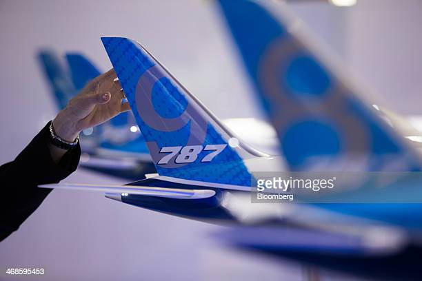 An attendee looks at a model of the Boeing Co 7879 Dreamliner aircraft on display at the company's booth at the Singapore Airshow held at the Changi...