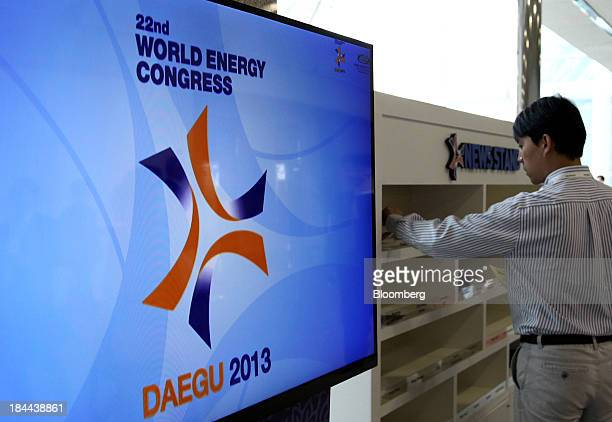 An attendee looks at a newspaper during the 22nd World Energy Congress in Daegu South Korea on Monday Oct 14 2013 The WEC a global conference on the...