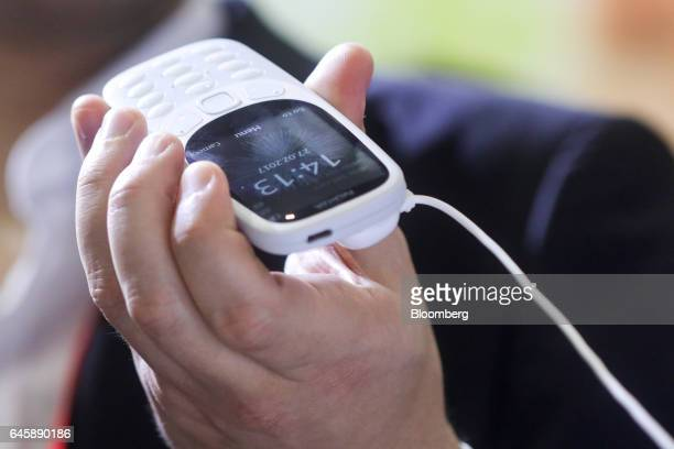 An attendee looks at a Nokia 3310 mobile phone manufactured by HMD Global Oy on the opening day of the Mobile World Congress in Barcelona Spain on...