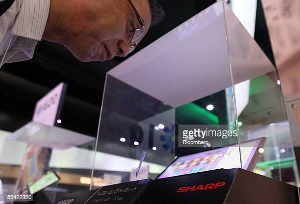 An attendee looks at a Sharp Corp tablet computer with a liquid crystal display screen based on indium gallium zinc oxide technology at the CEATEC...