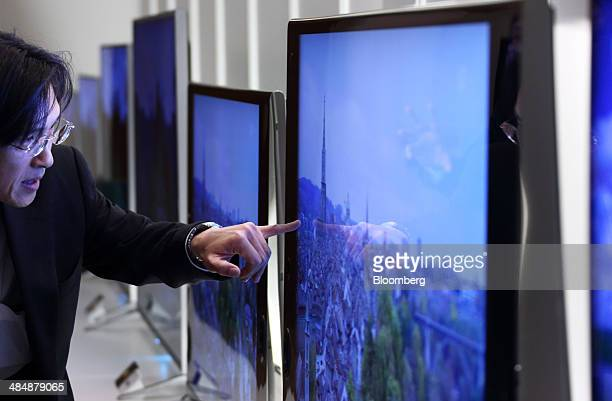 An attendee looks at a Sony Corp 4K Bravia liquidcrystaldisplay television displayed during an unveiling in Tokyo Japan on Tuesday April 15 2014 Sony...