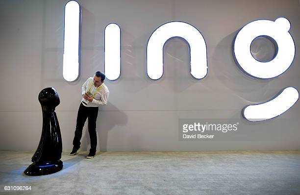 An attendee looks at a WaveBot service robot at the Ling booth at CES 2017 at the Las Vegas Convention Center on January 6 2017 in Las Vegas Nevada...